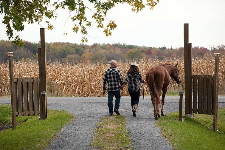 couple walking away with horse in country setting