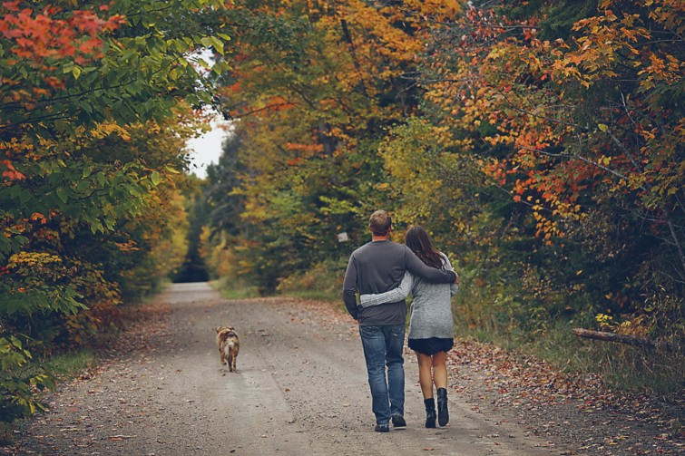 couple walking away with dog in country setting